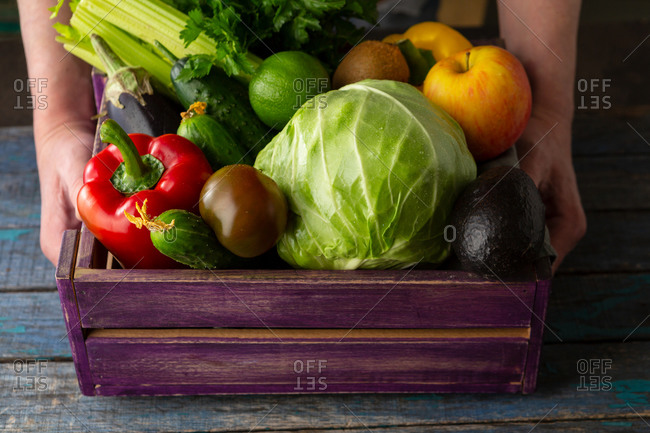 Vegetables in crate on wooden table in hands