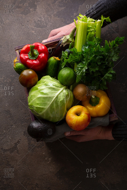 Fresh vegetables in crate in hands on stone surface