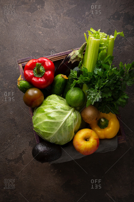 Fresh vegetables in crate on stone surface