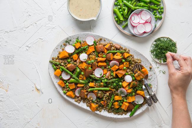 Adding fresh dill to a plant based grain salad