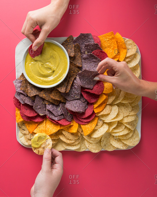Hands reaching for festive colored corn chips and dip