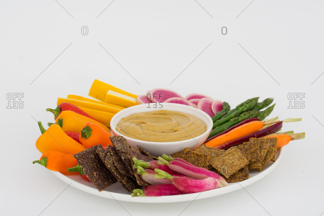 Vegan hummus with a variety of crisp vegetables and crackers