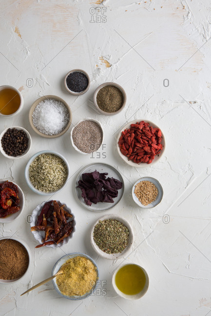 Many bowls of spices on a white countertop
