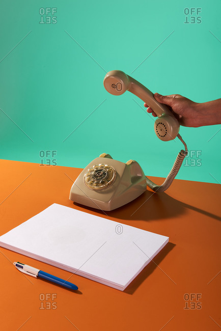 Unrecognizable person picking up telephone receiver to make a call