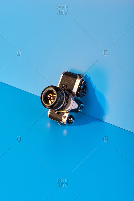 High angle view of vintage photo camera tilted on blue wall