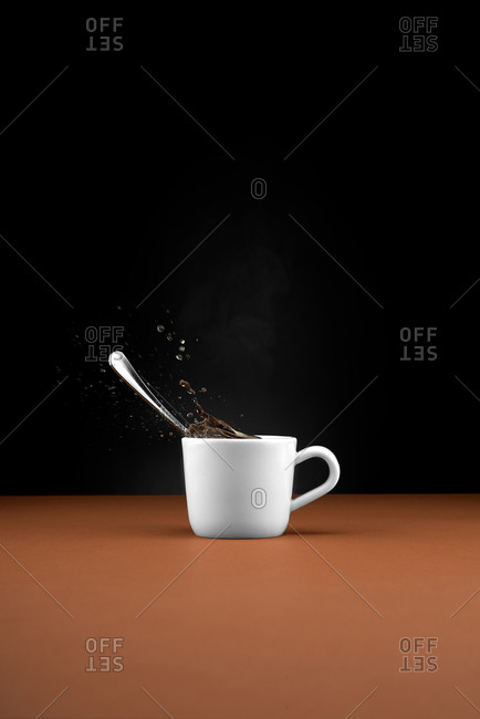 White ceramic cup with spoon and splashing hot beverage