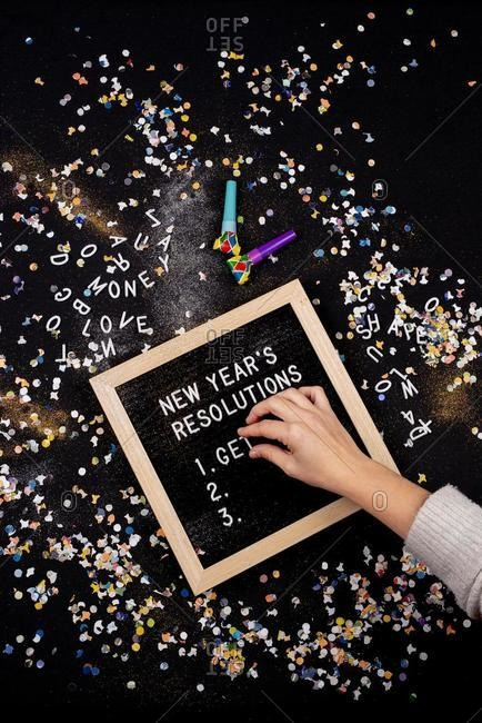 Person setting New Year's Resolutions on a letterboard surrounded by confetti and party blowers