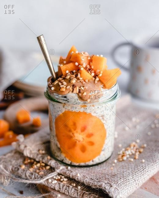 Jar of oatmeal with persimmon, peanut butter and chopped nuts