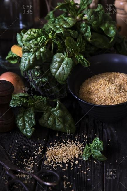 Spinach, onion, and bulgur wheat on a wooden table