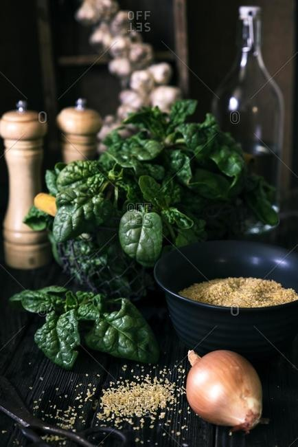 Spinach, onion, garlic, and bulgur wheat on a wooden table