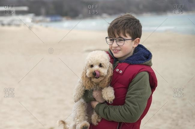 Boy standing on the beach carrying his dog, Bulgaria