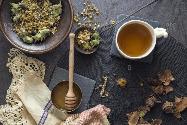 Mug of herbal tea with honey next to ingredients
