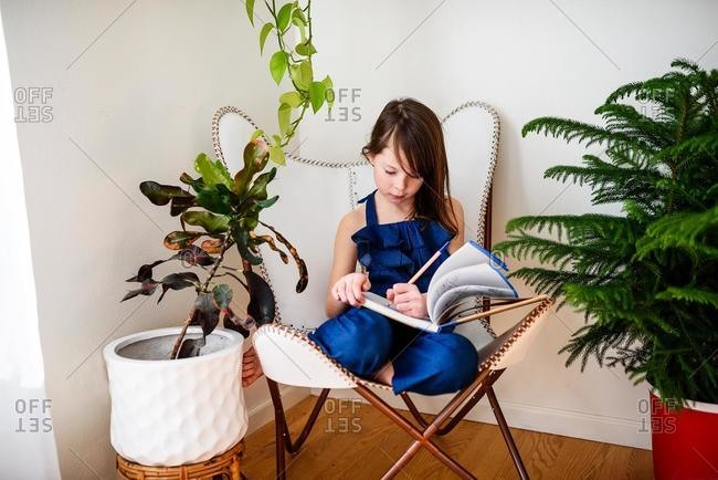 Girl sitting on a chair doing her homework