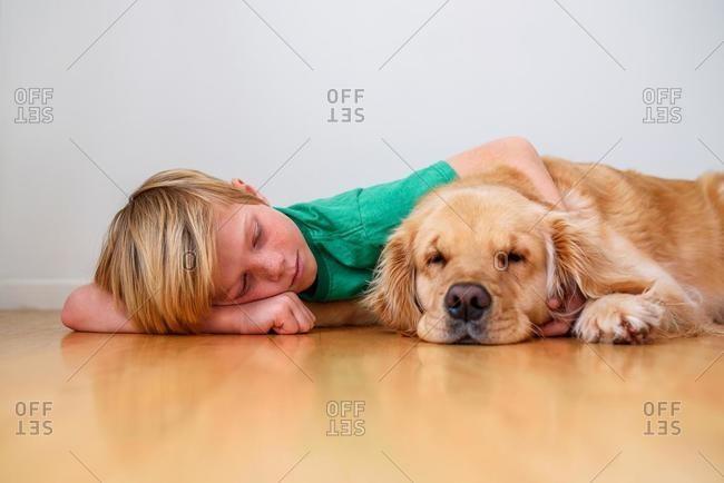 Boy lying on the  floor cuddling a golden retriever dog