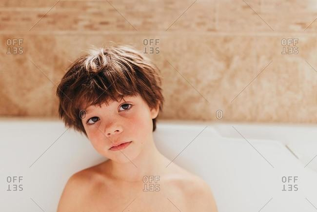 Portrait of a young boy sitting in a bubble bath