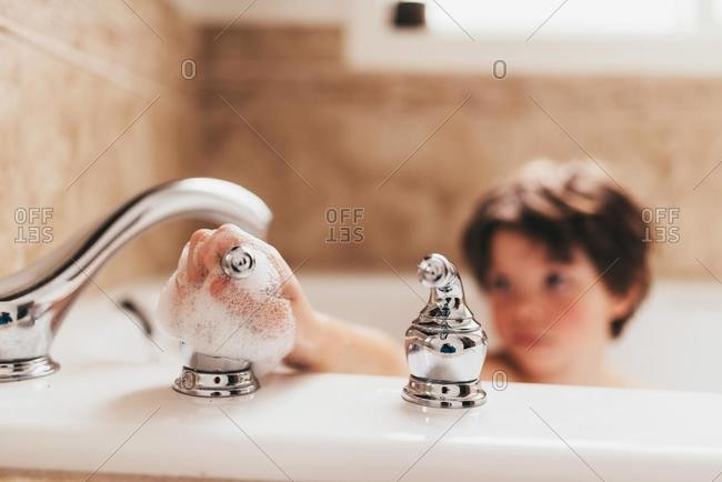 Boy in a bubble bath turning off the tap