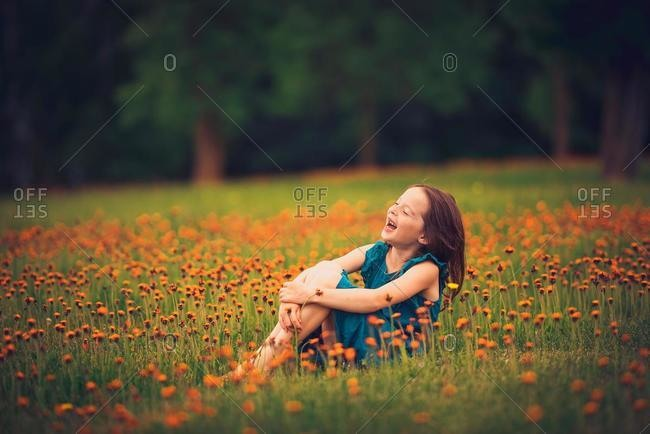 Happy girl sitting in a meadow with wildflowers laughing, USA