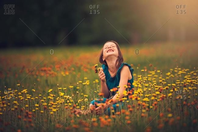Happy girl sitting in a meadow picking wildflowers, USA