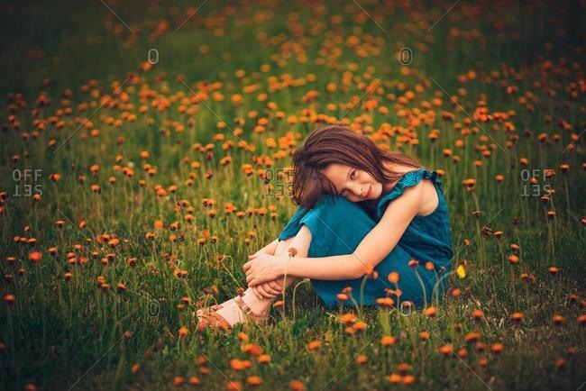 Happy girl sitting in a meadow with wildflowers, USA