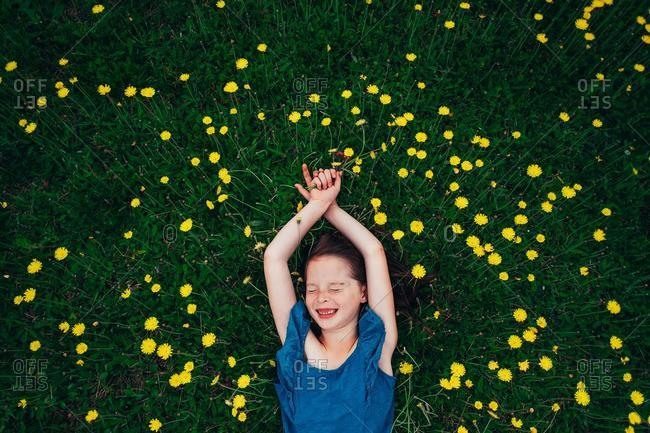 Overhead view of a happy girl lying in a meadow holding wildflowers, USA