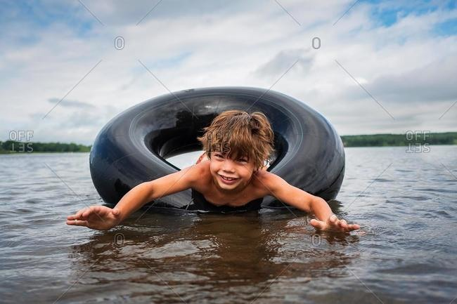 Happy boy floating in an inflatable rubber ring in a lake, USA