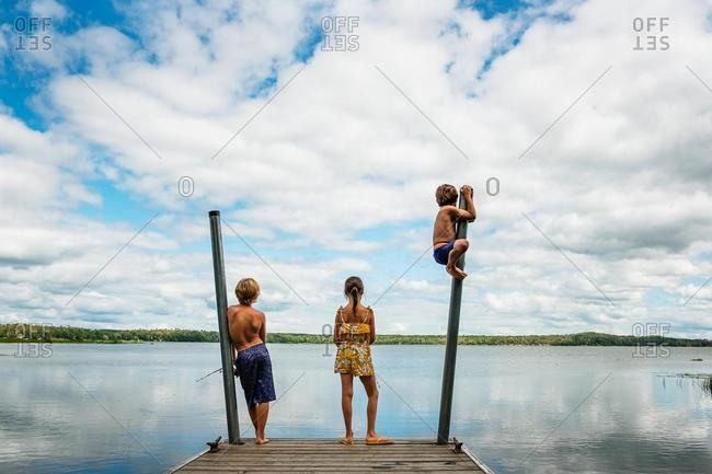 Three children standing on a dock fishing and messing about, USA