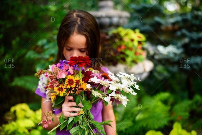 Portrait of a girl standing in a garden smelling a bunch of flowers, USA