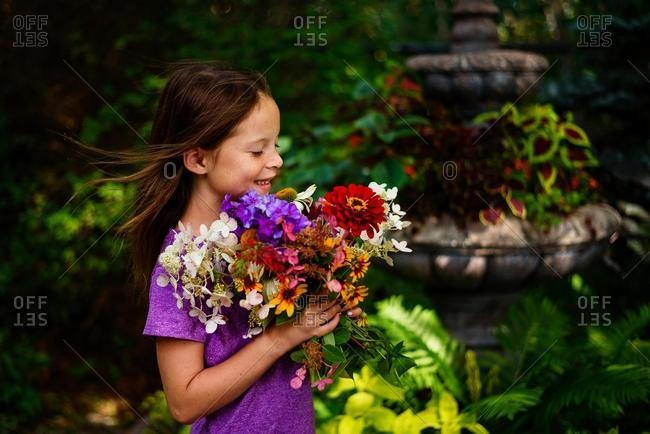Portrait of a smiling girl standing in a garden holding a bunch of flowers, USA