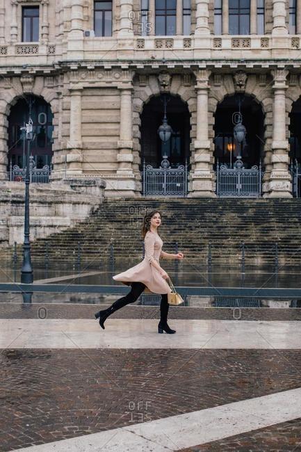 Woman running through the city, Rome, Lazio, Italy