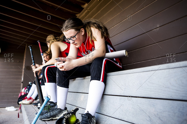Young female softball player looking at mobile phone in dugout