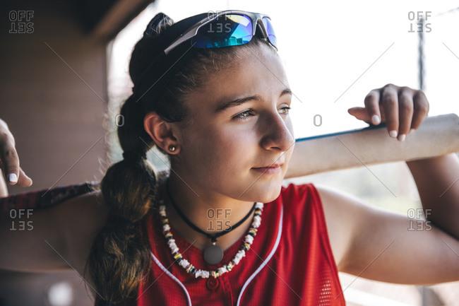 Portrait of teenage softball player holding bat behind head
