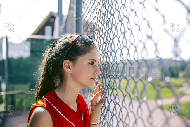 Portrait of middle school softball player standing near fence in dugout
