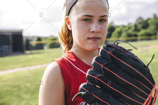 Portrait of confident softball player holding glove on baseball field