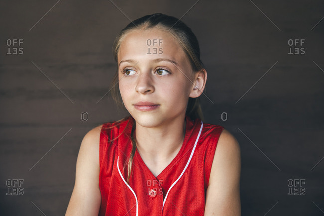 Portrait of teenage softball player sitting in dugout