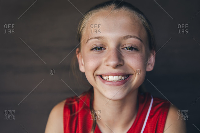 Portrait of happy teenage softball player sitting in dugout