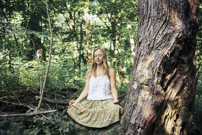 Woman in skirt meditating at forest