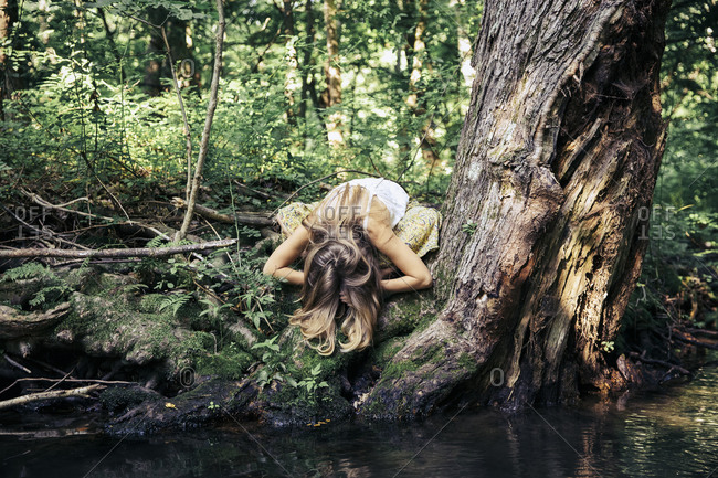 Woman bowing her head down while meditating in forest.