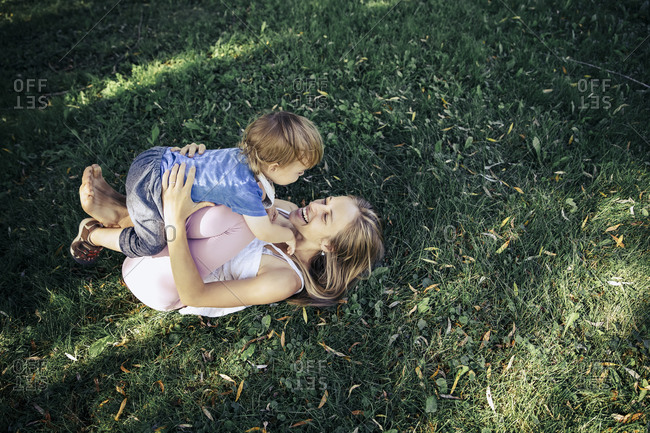 Woman lifting her son while lying down on grass in a park.