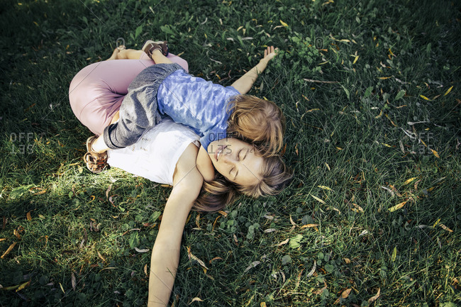 Son hugging her mother while she is lying down on grass in a park.