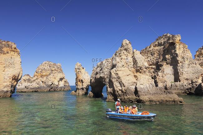 June 7, 2017: Tourist boat exploring the rocky coast at Ponta da Piedade near Lagos, Algarve, Portugal