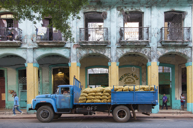 March 9, 2015: Caribbean, Cuba, Havana, La Habana, blue potato truck in front of an old house facade