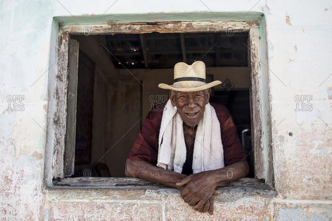 Street scene, old man looks out the window, portrait, Trinidad, Cuba