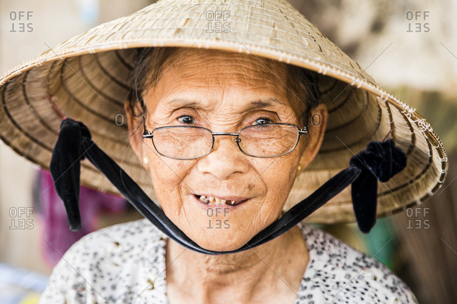 Woman with traditional hat and glasses, portrait, market in Hoi An, Vietnam