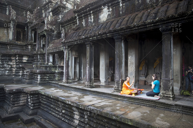 October 11, 2017: Siem Reap, Angkor, Angkor Wat Temple, a monk speaks for a dollar a prayer for a tourist