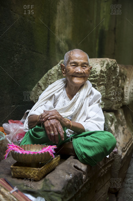 Siem Reap, Angkor, Temple Preah Khan, old lady prays for you and then ties a ribbon around your hand