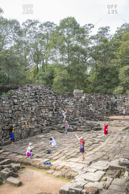 October 10, 2017: Siem Reap, Angkor, Bayon Temple, overrun by tourists, tourist while taking pictures