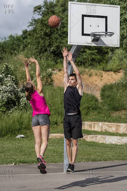 Young couple is playing basketball