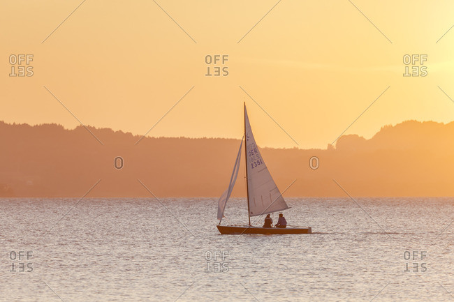 October 1, 2015: Sailboat on the Chiemsee behind it the Chiemgau Alps, Ubersee, Chiemgau, Upper Bavaria, Bavaria, southern Germany, Germany, Europe