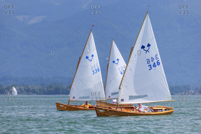 July 11, 2015: Segler Chiemseeplatte on the Chiemsee behind it Chiemgau Alps, Chiemgau, Upper Bavaria, Bavaria, southern Germany, Germany, Europe