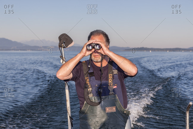July 1, 2015: Fisher Thomas Lex from the Fraueninsel at the morning exit on the Chiemsee, Frauenchiemsee, Chiemgau, Upper Bavaria, Bavaria, southern Germany, Germany, Europe